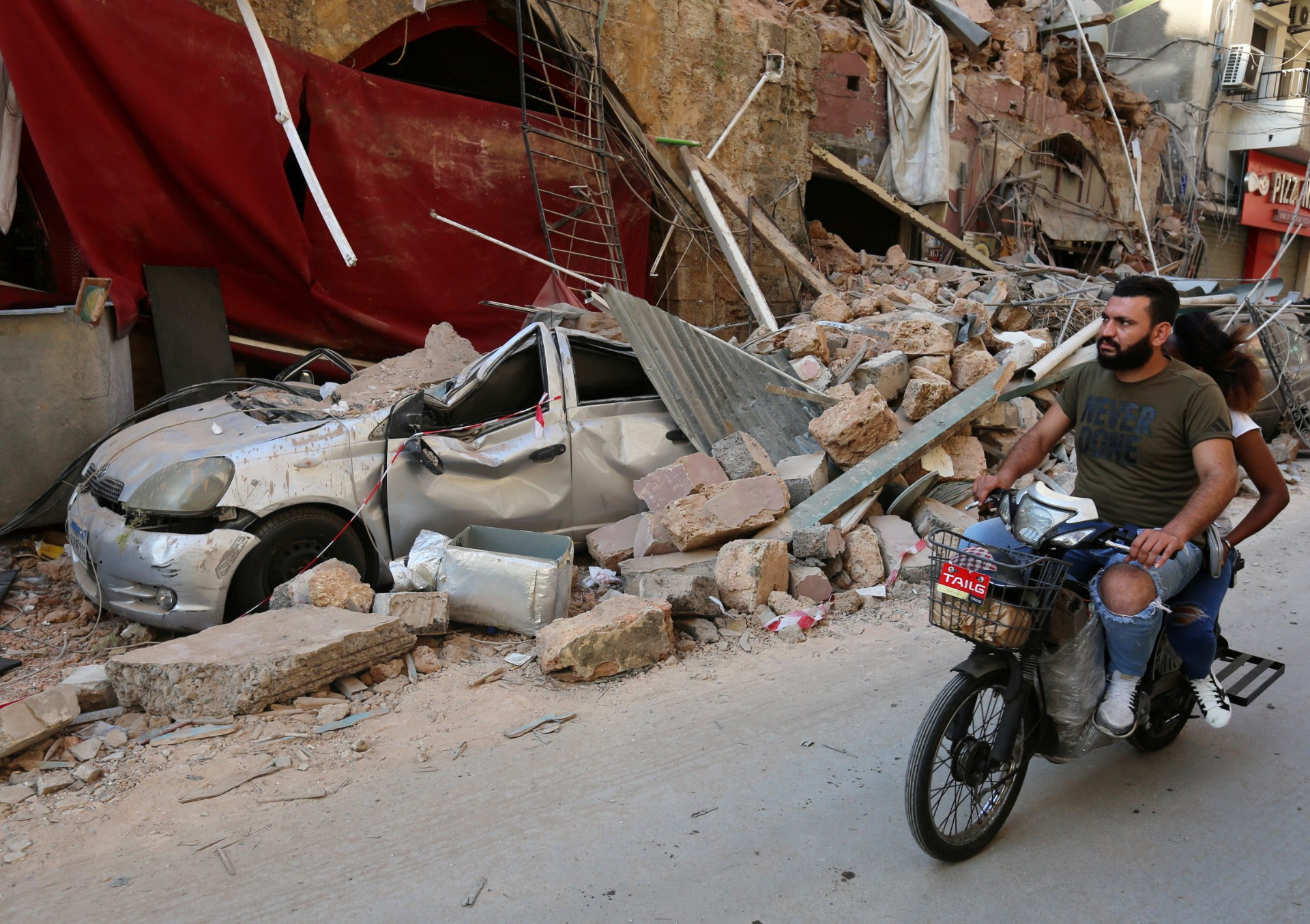 A man rides on a motorbike near rubble from damaged buildings in Gemmayzeh (Reuters)