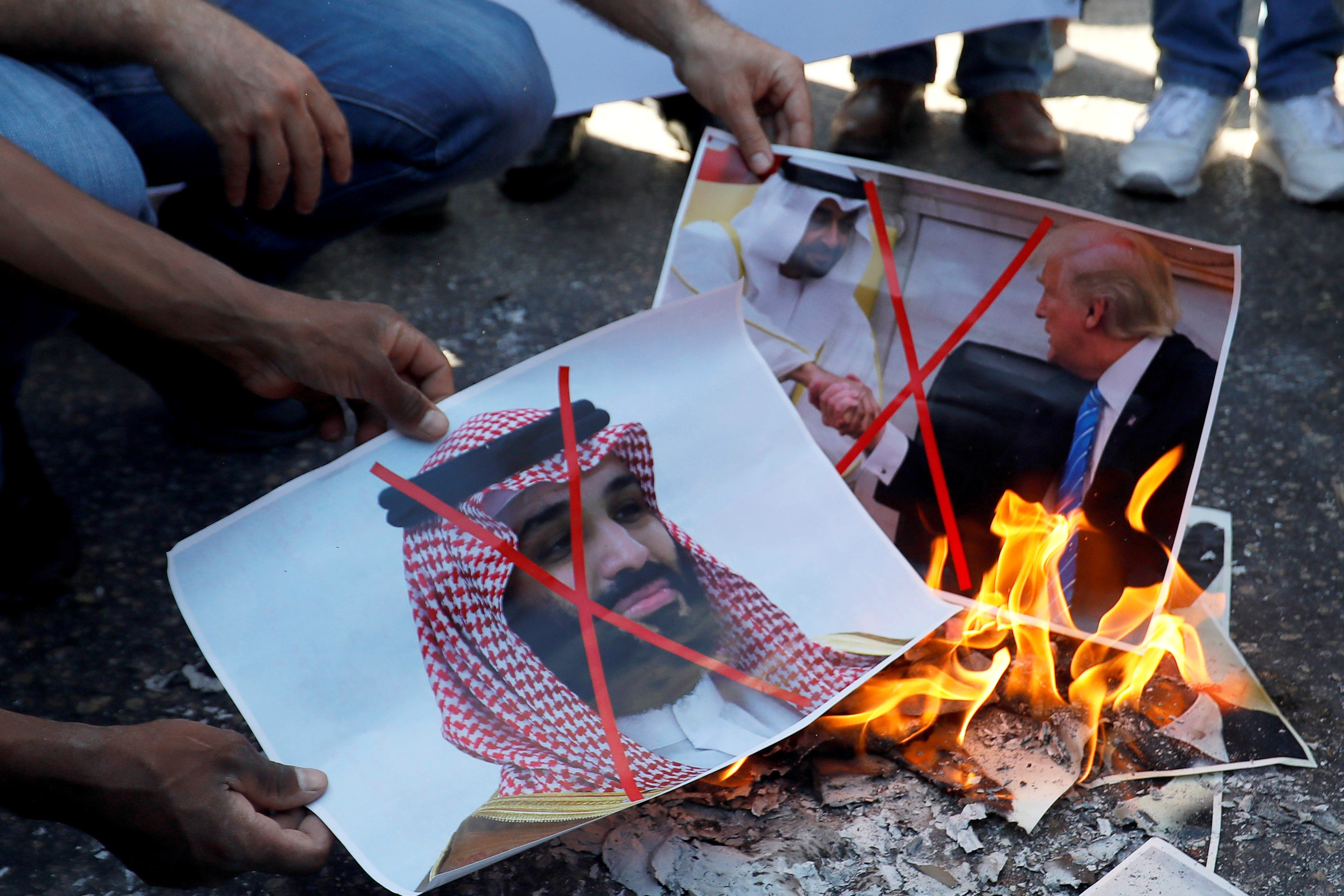 Palestinians burn pictures depicting US President, Abu Dhabi Crown Prince and Saudi Arabia's Crown Prince during a protest against the UAE deal with Israel in Ramallah on 15 August (Reuters)