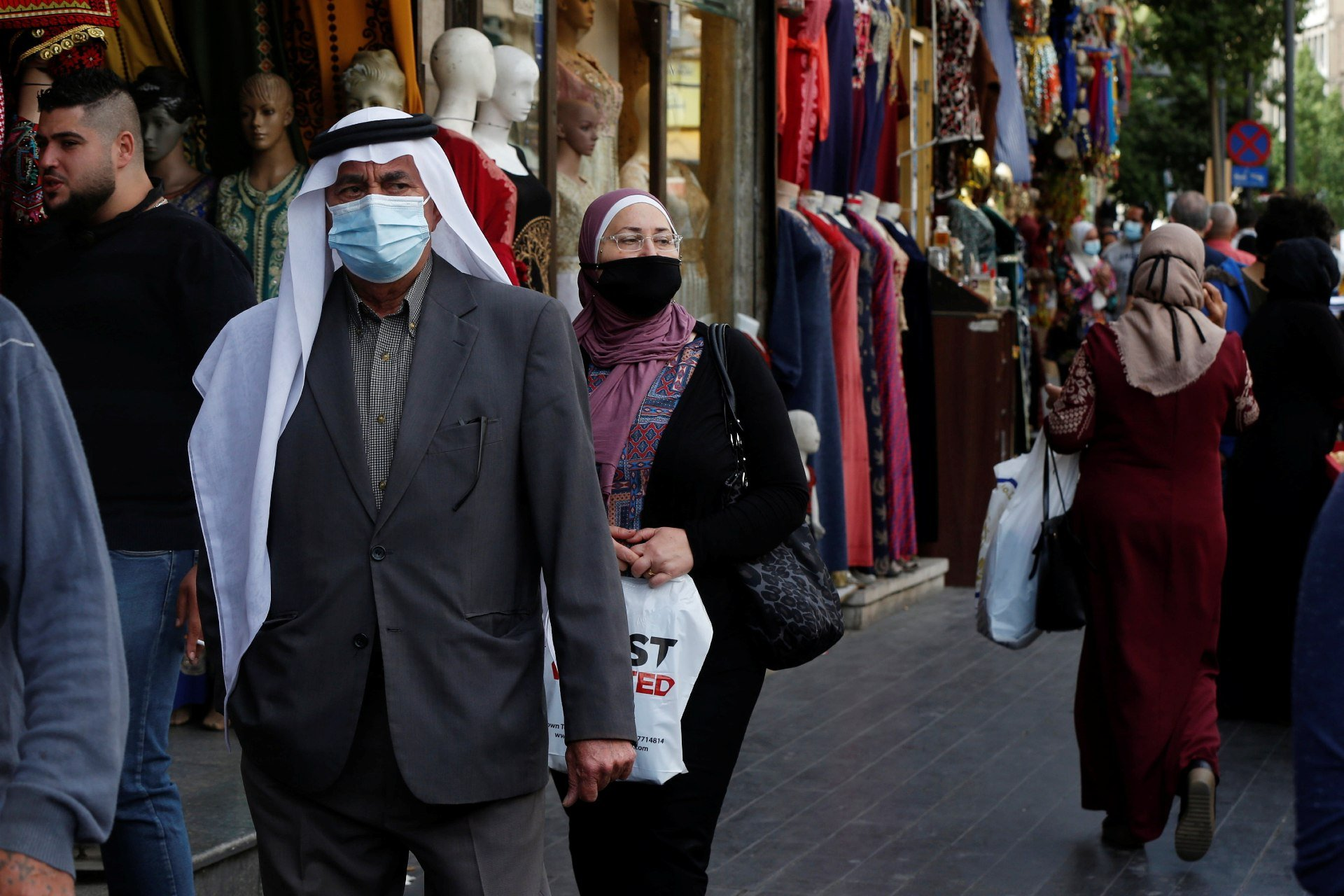 People, some wearing protective masks, walk in downtown Amman, amid fears over rising numbers of the coronavirus disease (Reuters)