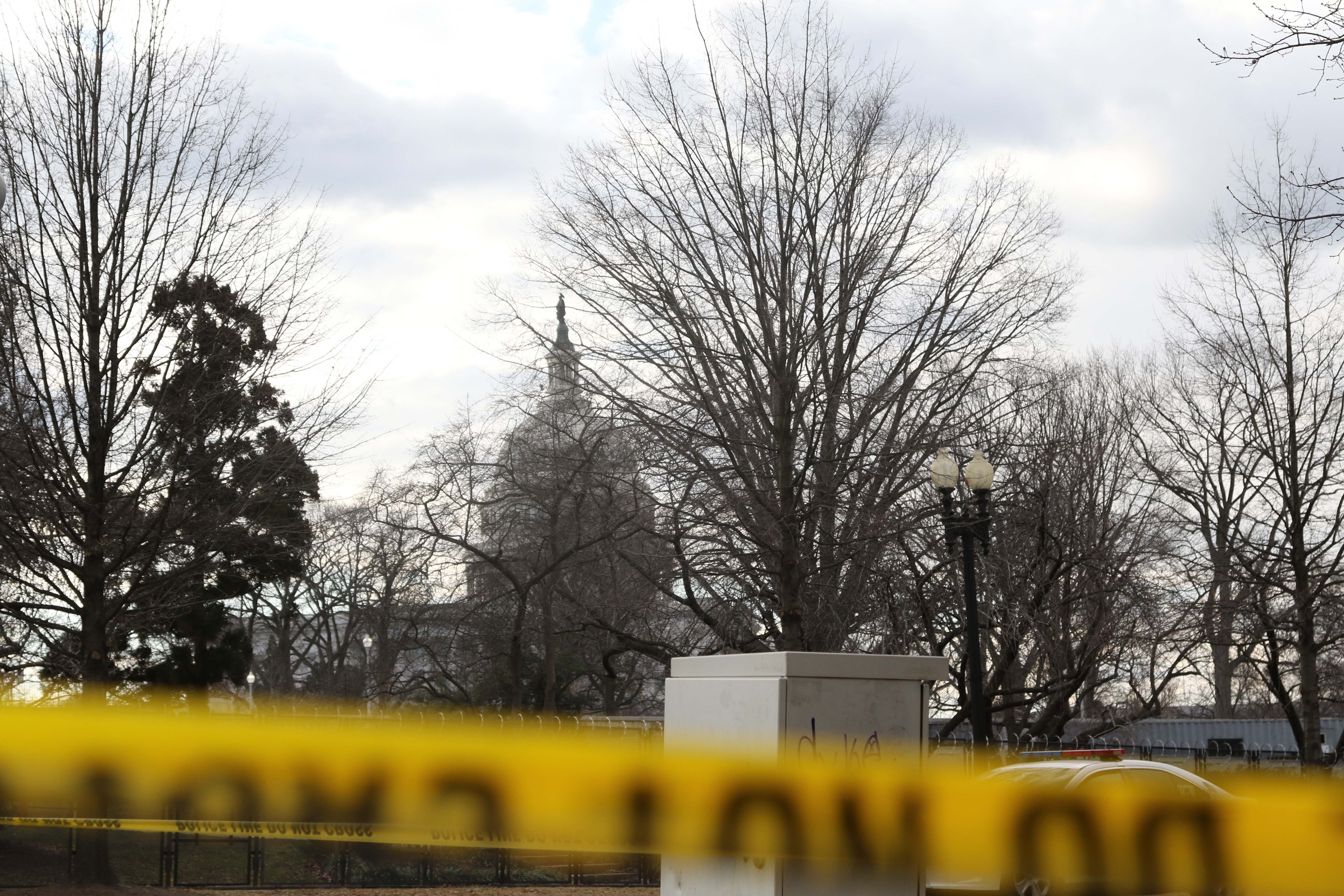 The top of the US Capitol building seen from behind fencing and caution tape.