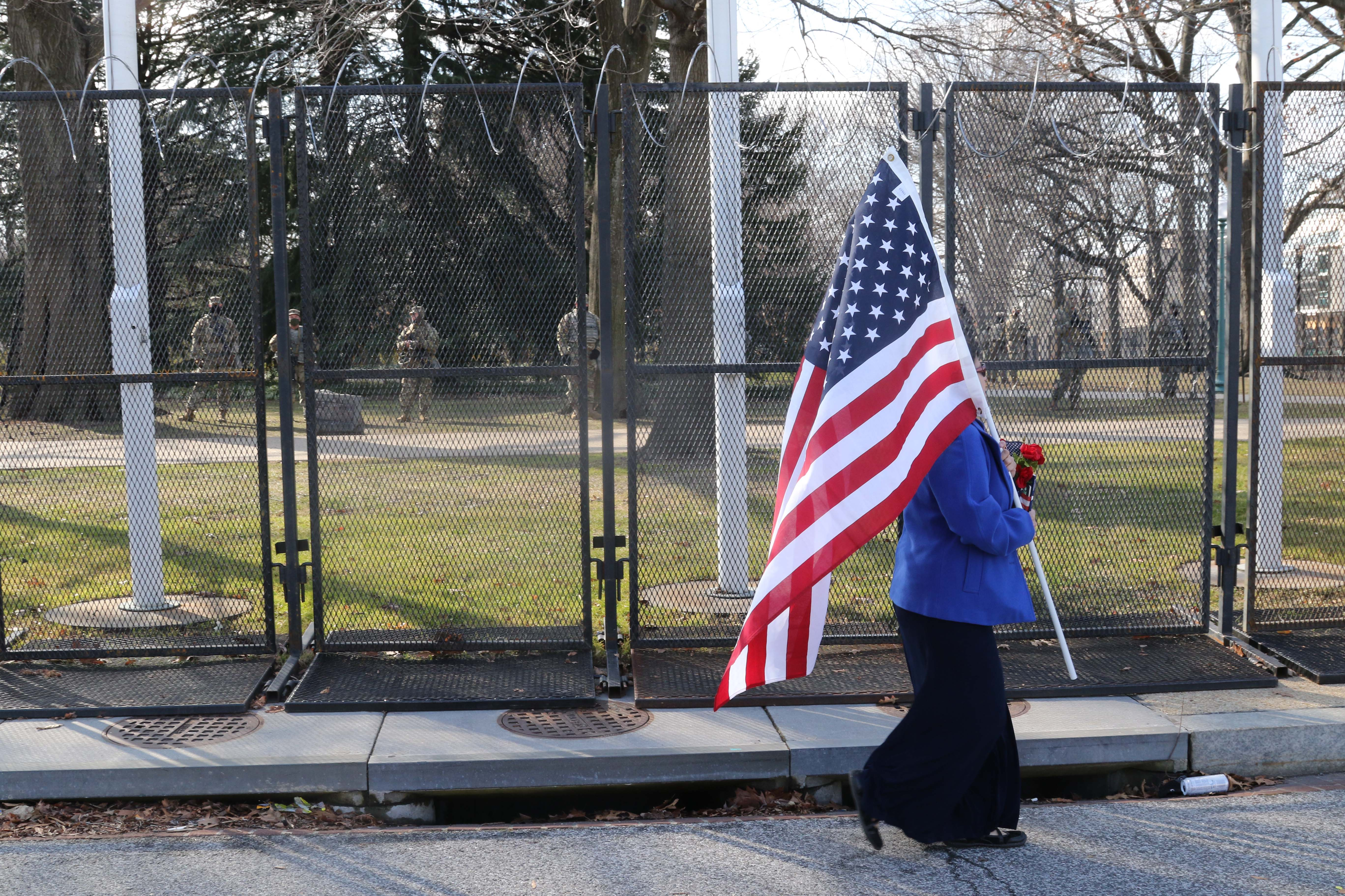 A woman walks past a line of soldiers while carrying the American flag.