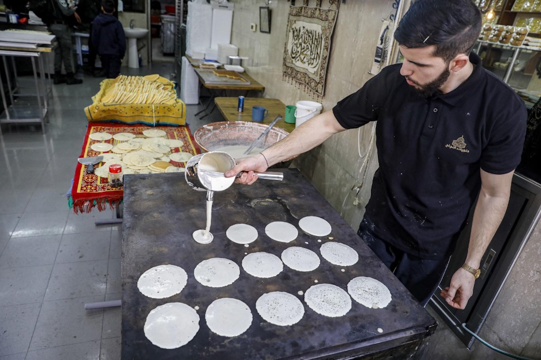 JÉRUSALEM. Un chef palestinien prépare des qatayefs, boulettes traditionnelles préparées par les vendeurs de rue ainsi que par les ménages du Levant et de l'Égypte pendant le Ramadan, dans un magasin de la vieille ville de Jérusalem le 12 avril 2021 (AFP)
