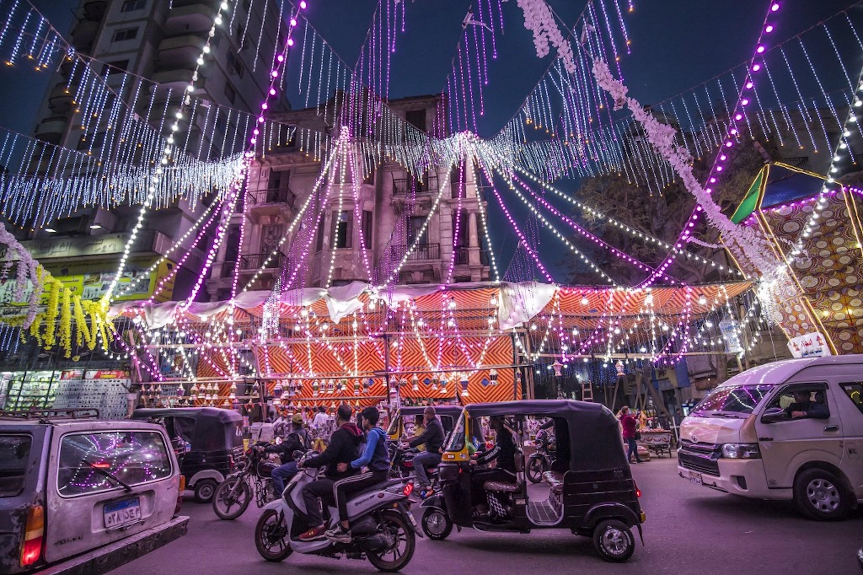 ÉGYPTE. Des véhicules, des motos et des tuk-tuks (pousse-pousse motorisés) passent devant un étal vendant des lanternes du Ramadan le long d'une rue principale de Chubra, dans la banlieue nord du Caire, le 12 avril 2021 (AFP)