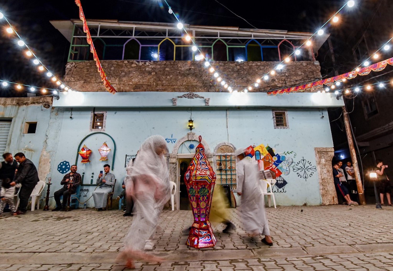 IRAK. Des enfants dansent autour d'une lanterne lors d'une fête de rue organisée par une ONG culturelle locale lors de la première nuit du Ramadan dans la vieille ville de Mossoul, le 13 avril 2021 (AFP)
