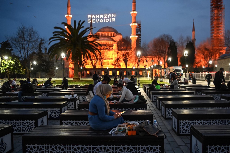 TURQUIE. Les musulmans partagent l'iftar, sur la place Sultanahmet, avec la mosquée bleue en arrière-plan, à Istanbul le 13 avril 2021 (AFP)