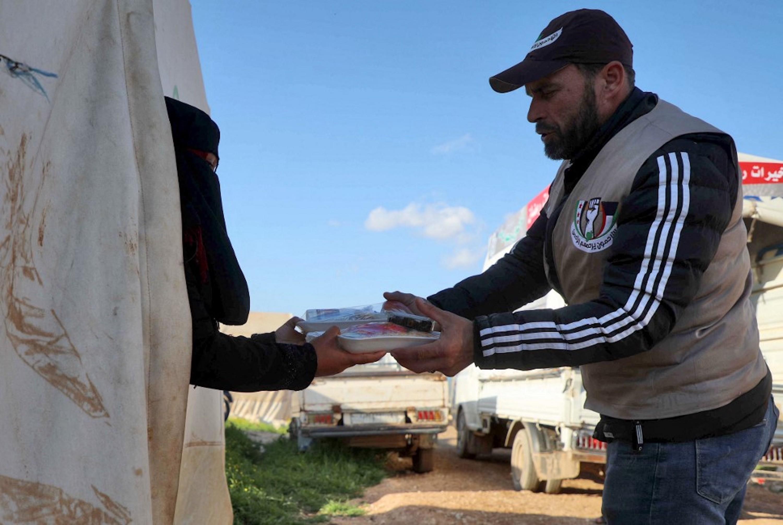 SYRIE. Un volontaire syrien distribue des assiettes de nourriture préparées par une organisation caritative locale pour l'iftar, dans un camp pour personnes déplacées par le conflit dans la ville de Sarmada, dans la province d'Idleb, au nord-ouest de la Syrie, le 13 avril 2021 (AFP)