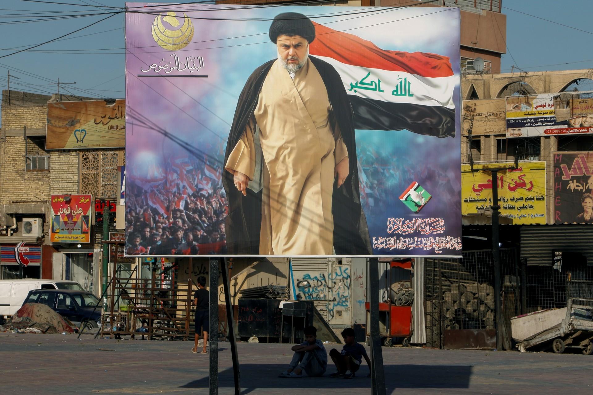 Iraqi boys sit under a poster of Moqtada al-Sadr in the Sadr City district of Baghdad (Reuters)