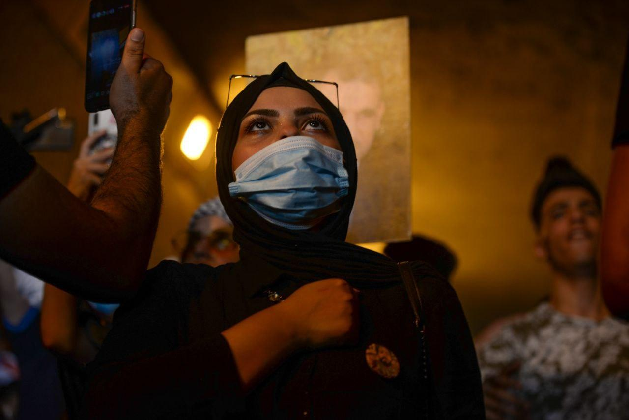 A women protester wearing a mask and giving the respect of the national anthem a day before the anniversary of Iraq's 2019 protests.