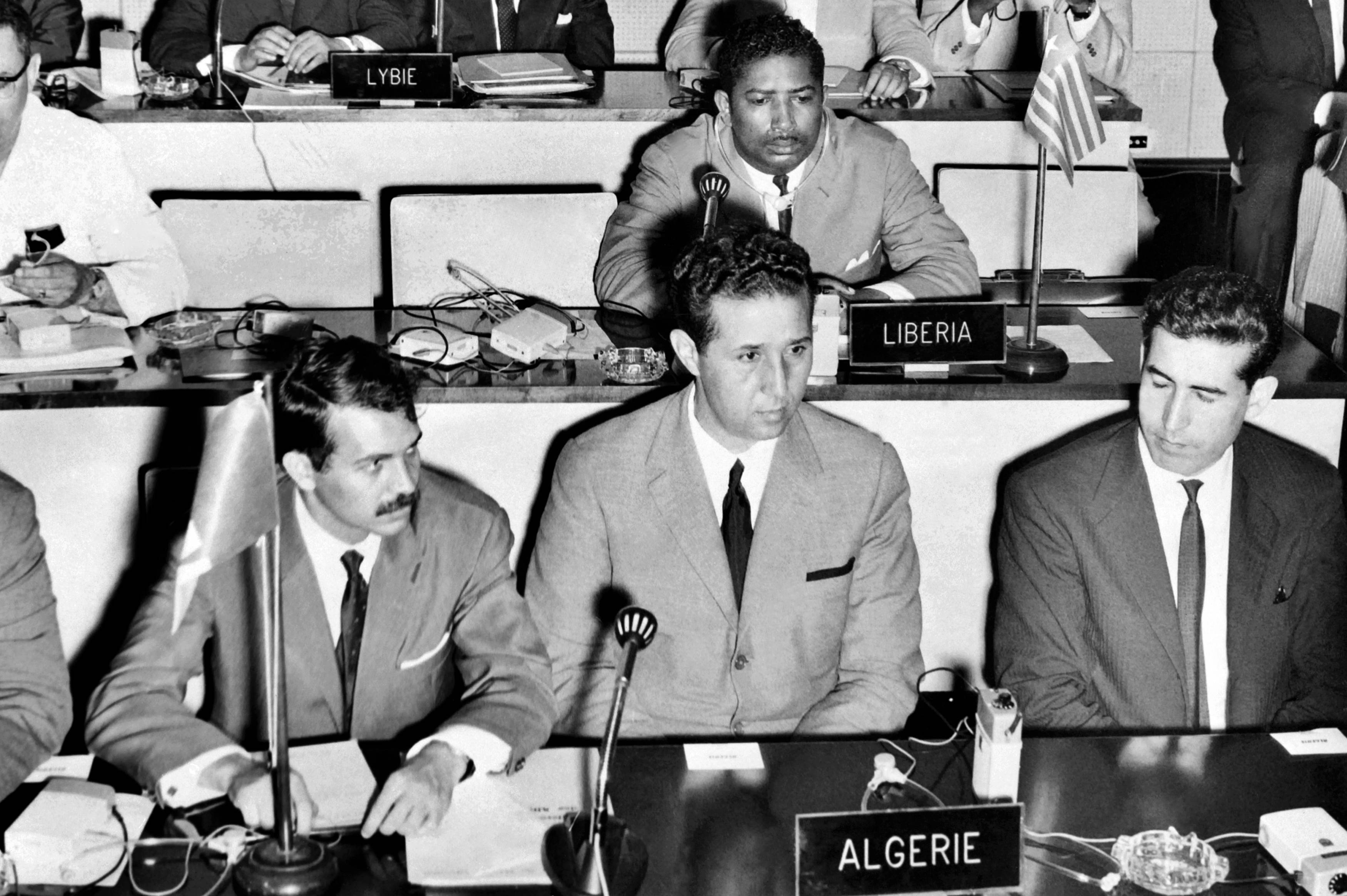 Bouteflika, left, then the minister of youth, sport and tourism, sits next to President Ahmed Ben Bella during a meeting of the Organisation of African Unity in Senegal in August 1963 (AFP)