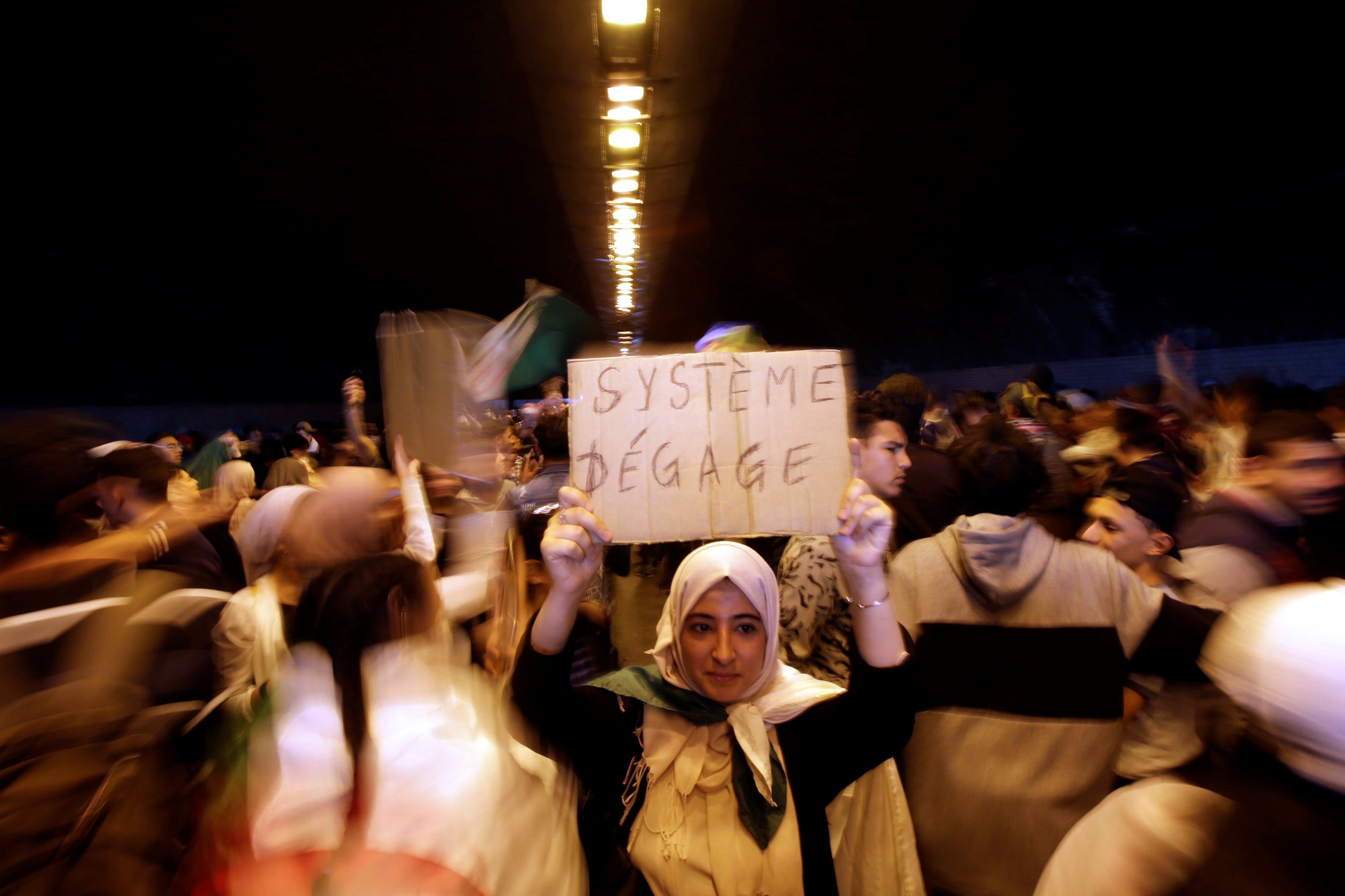A demonstrator in Algiers holds a sign reading 'Out with the system' (Reuters/File photo)