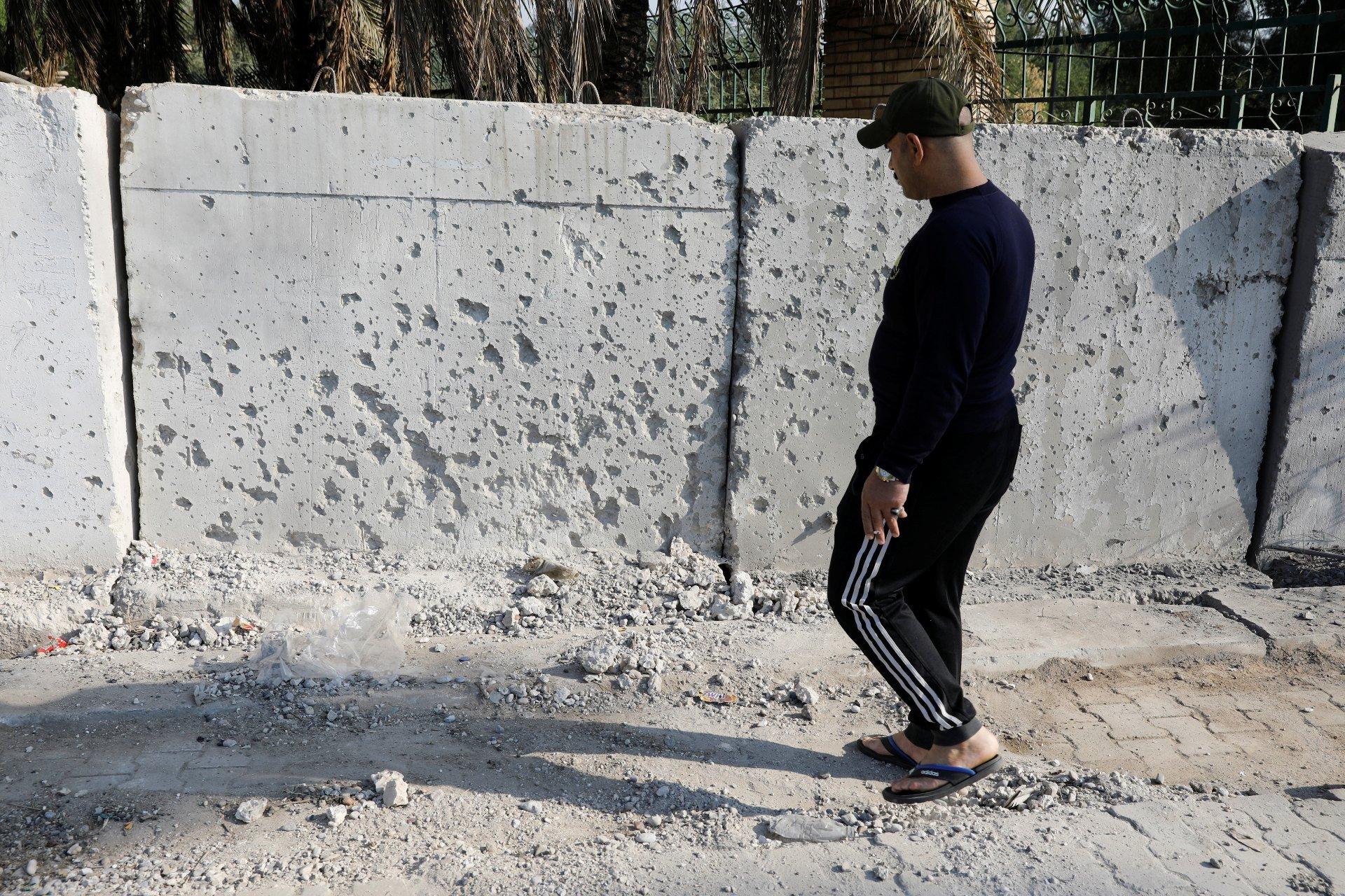 Un homme observe les dégâts d'une attaque à la roquette dans la zone verte de Bagdad (Reuters)