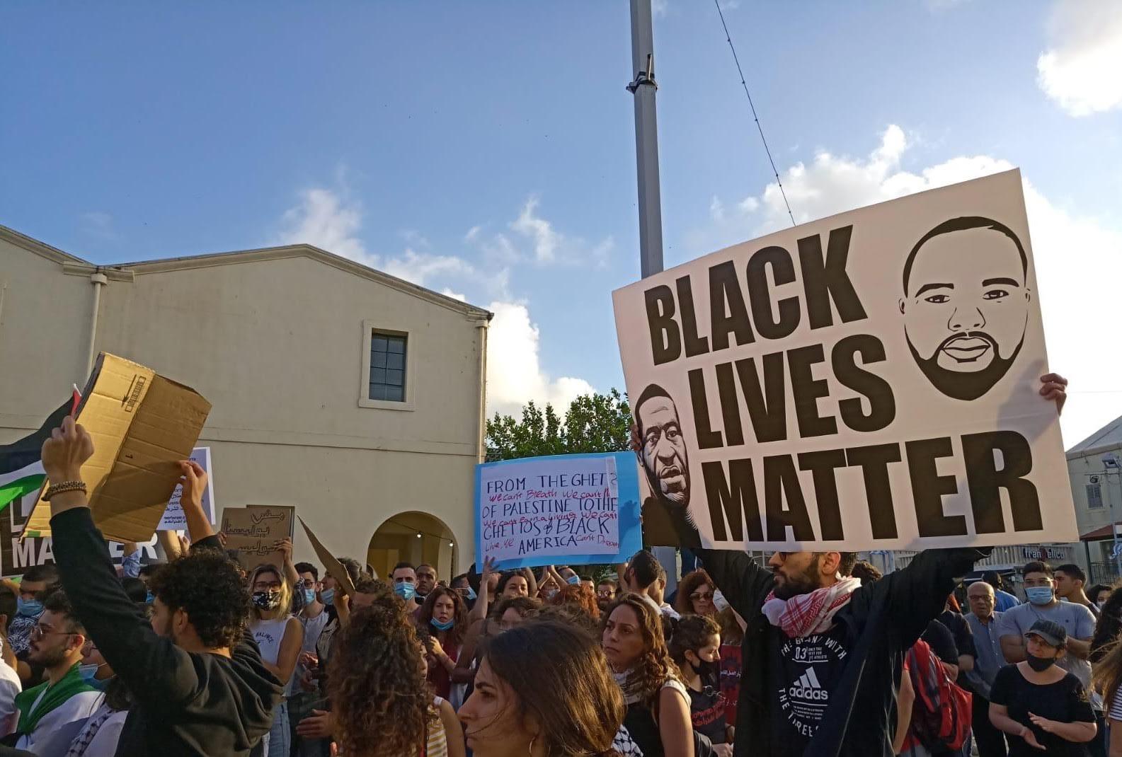 Un manifestant brandit un manifestant Black Lives Matter à Haïfa le 2 juin (MEE)