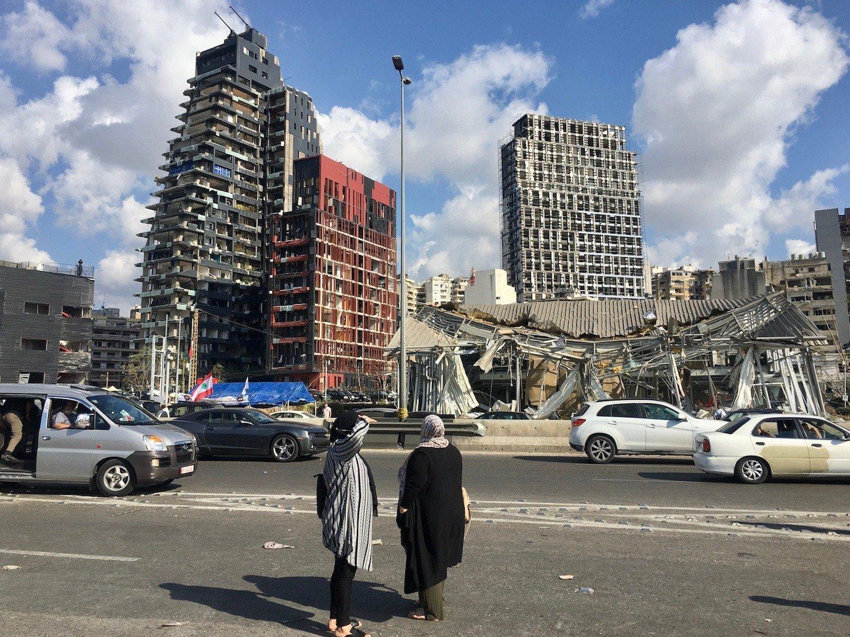 Yoldan geçenler Beyrut limanı yakınlarındaki hasarlı binaya bakıyor (MEE / Chloe Domat)