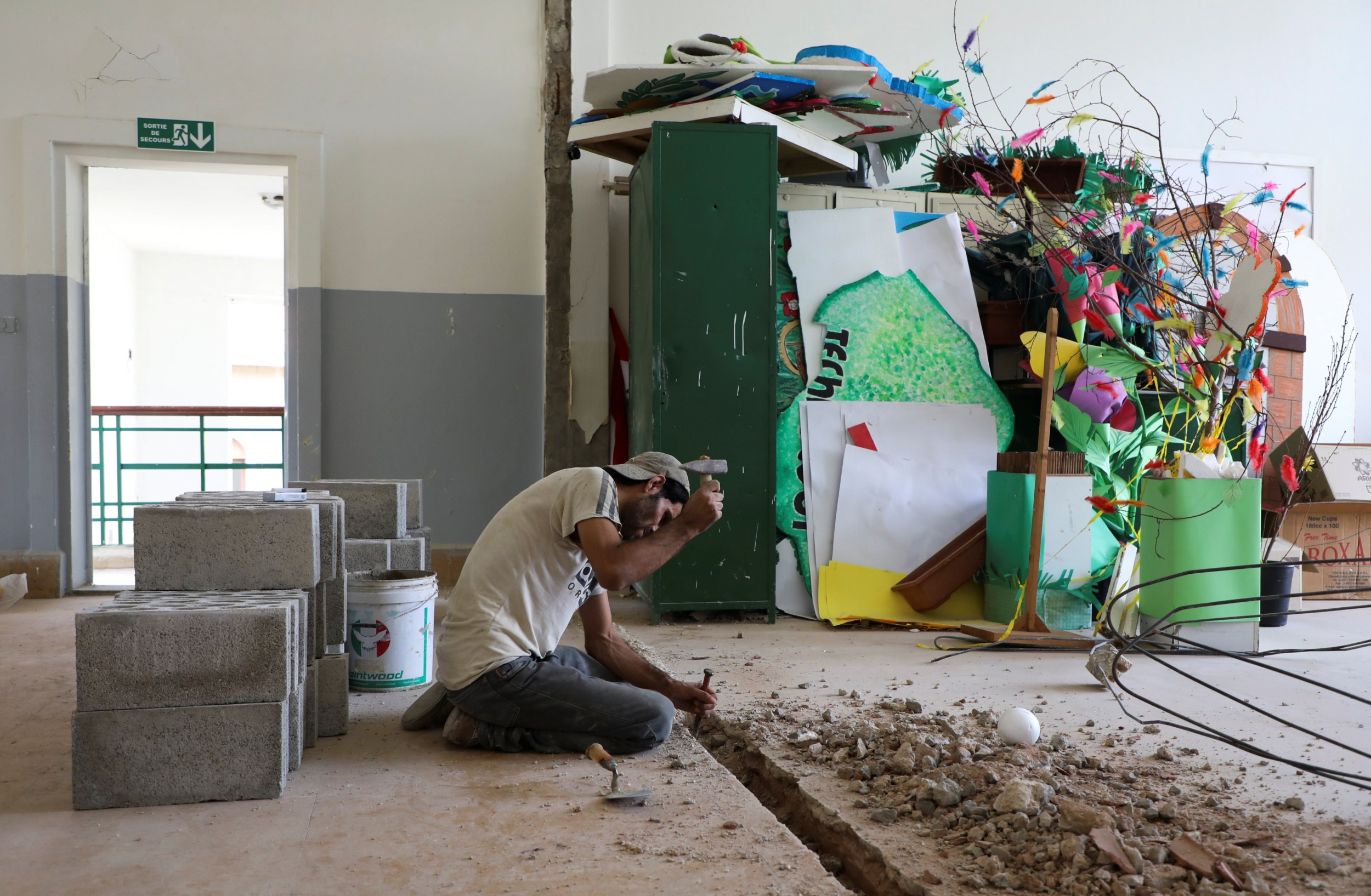 A man works on repairs inside Sagesse Beyrouth school on 24 September 2020, which was damaged due to the explosion at the Beirut port on 4 August 2020. (Reuters)