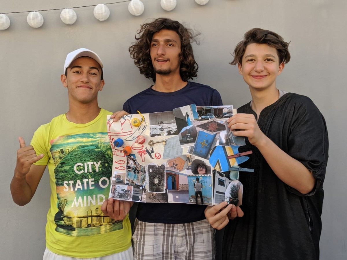 Brooke Benoit's two homeschooled sons, Badier (C) and Amine (R), with their friend Soulaiman Ouknart (L), display a vision board they created for a school project (Amine Benoit-Elkaoui)