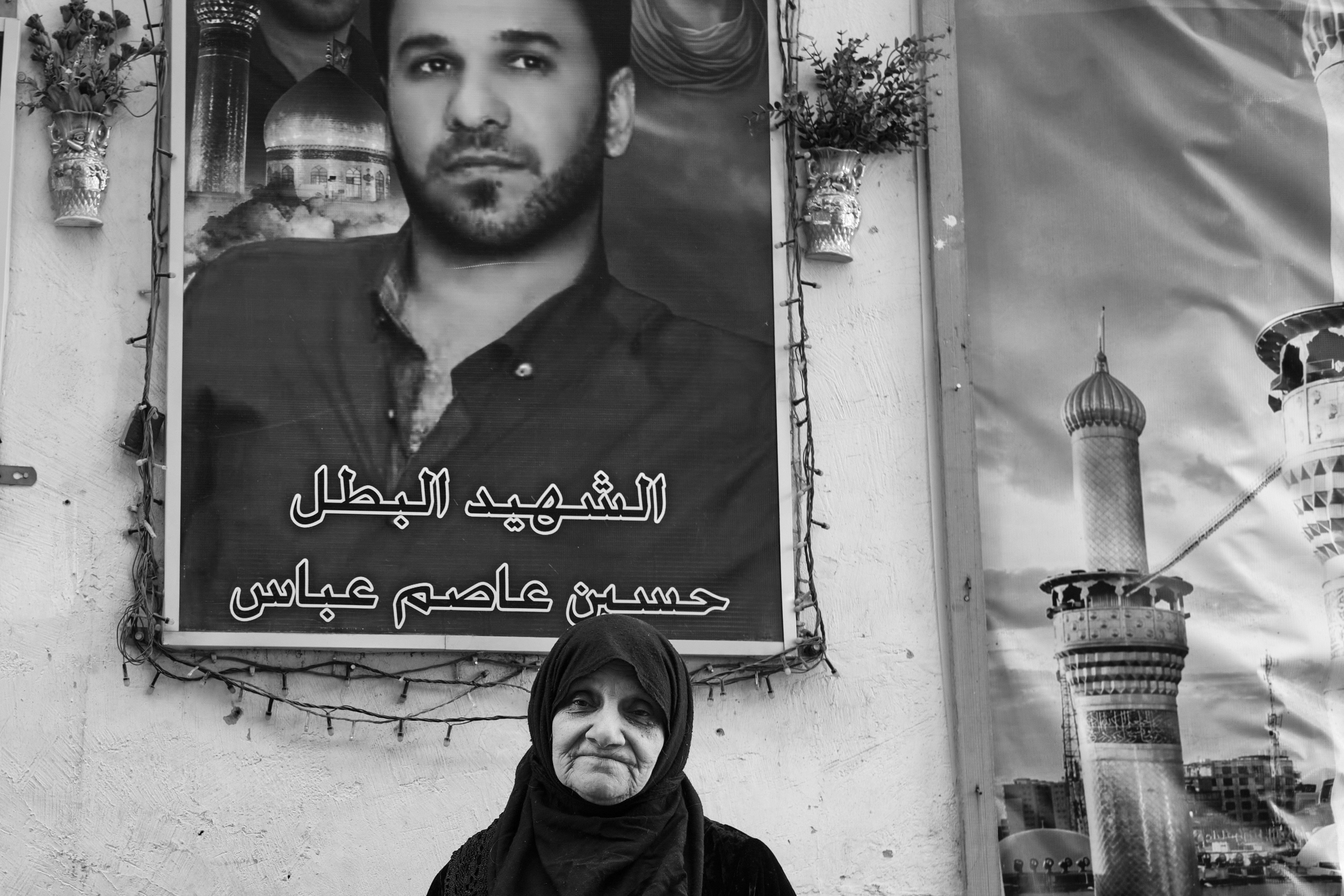 An Iraqi woman standing next to her maryred son's portrait in Baghdad on 25 February, 2021 (Photo by Nabil Salih)
