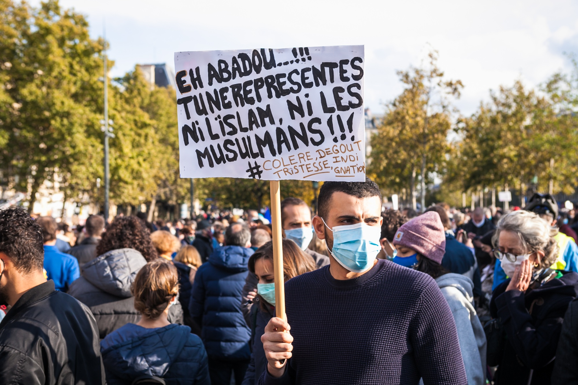 "A demonstrators holds a sign addressed to the killer of Samuel Paty reading ""Hey Abadou, you don't represent Islam nor Muslims"" during a rally in Paris on  on 18 October 2020 (Reuters)"