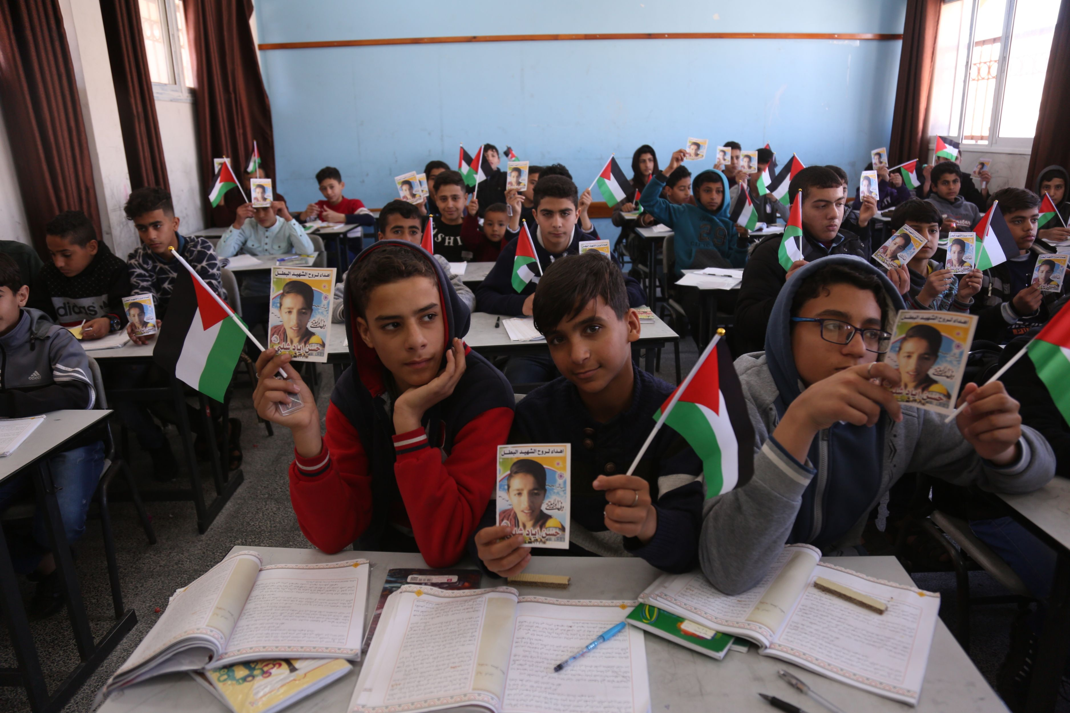 Hassan's classmates hold up photos of the slain boy (MEE/Samar Abu Elouf)