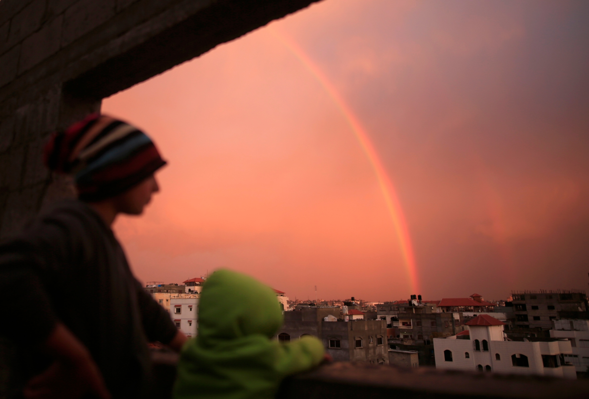 Caption: Palestinian children look at a rainbow appearing over Gaza City on 15 February 2017 (AFP)