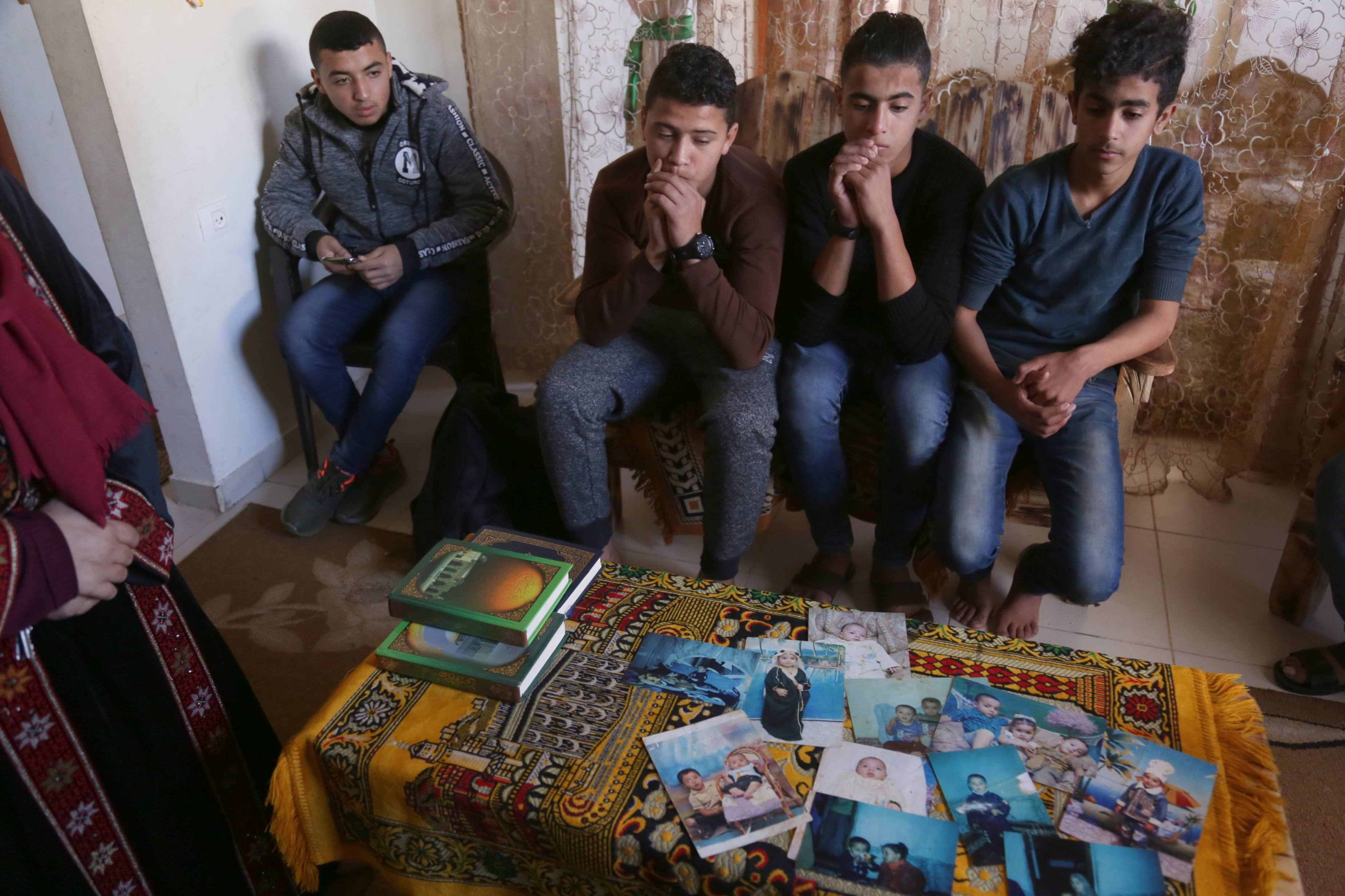 Abdel Fattah Shalabi, 16, Ahmed Abu Ramadan, 15, Rasmi Abu Sabala,16, and Ahmed Abu Qusai, 14, look at childhood pictures of Hassan (MEE/Samar Abu Elouf)