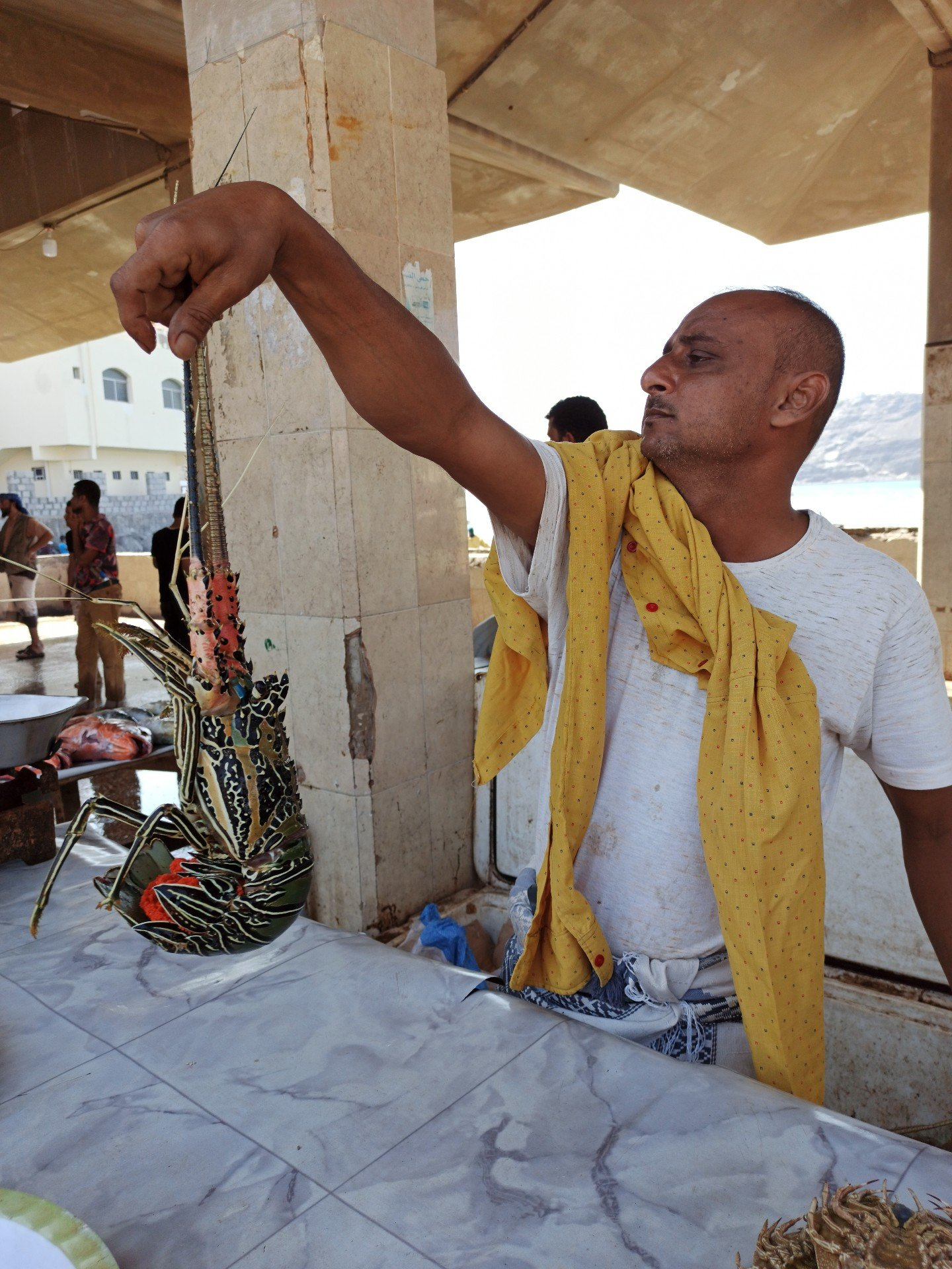 A fisherman sells a lobster in Aden province's Sirah, southern Yemen (MEE)
