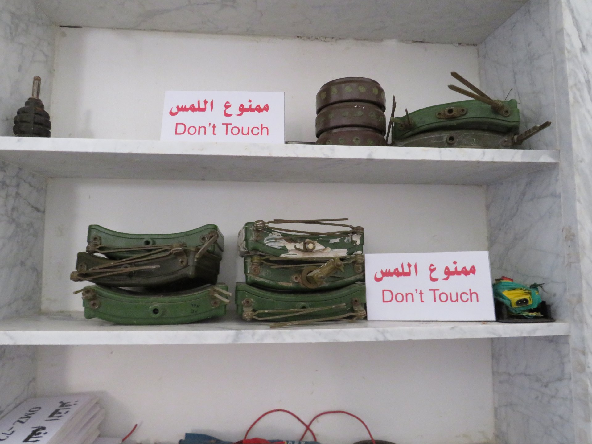 Eight MON-50 mines displayed on a shelf in a Tripoli military base (MEE/Daniel Hilton)