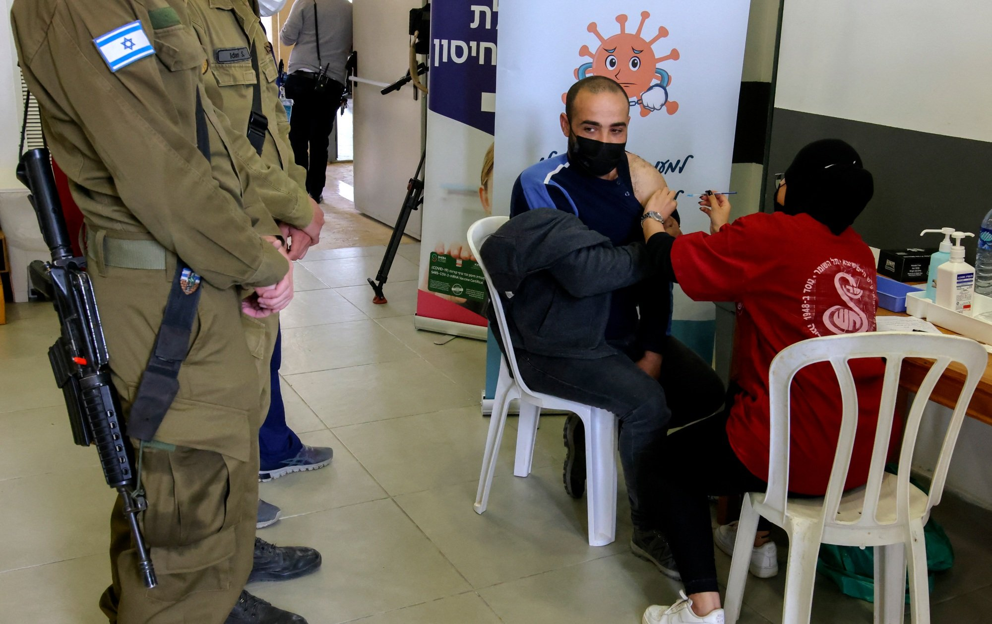 An Israeli paramedic administers the Covid-19 vaccine to a Palestinian working in Israel at the Shaar Ephraim checkpoint between Israel and the occupied West Bank near Tulkarem on 8 March 2021 (AFP)