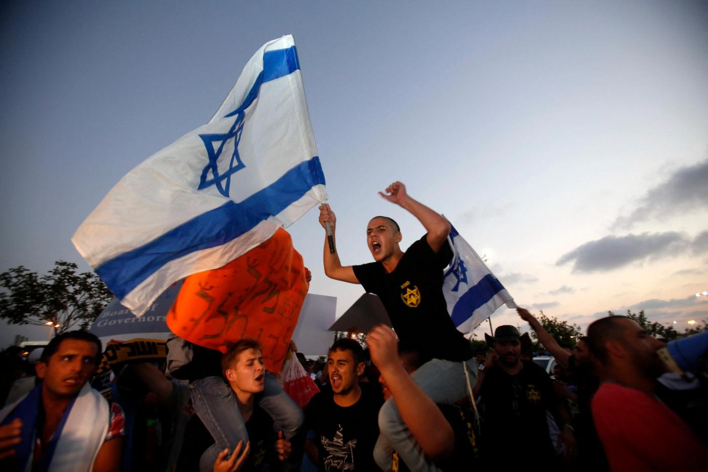 Lehava supporters chant slogans against the wedding of a Palestinian citizen of Israel and a Jewish-Israeli on 17 August 2014 (AFP)