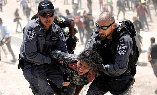 Israeli policemen detain a Palestinian girl in Khan al-Ahmar, West Bank on 4 July 2018 (Reuters)