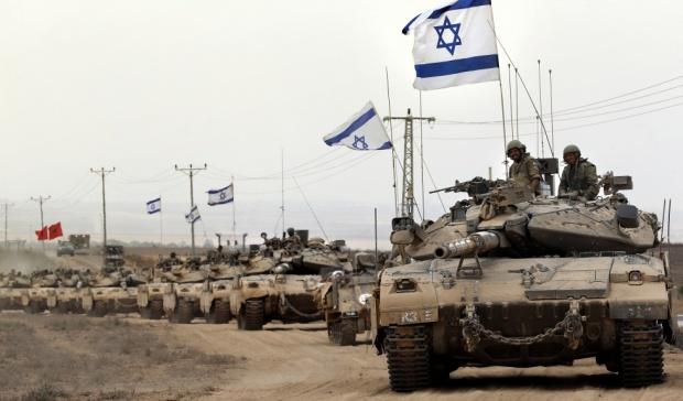 Israeli soldiers on tanks fly their national flag (AFP)
