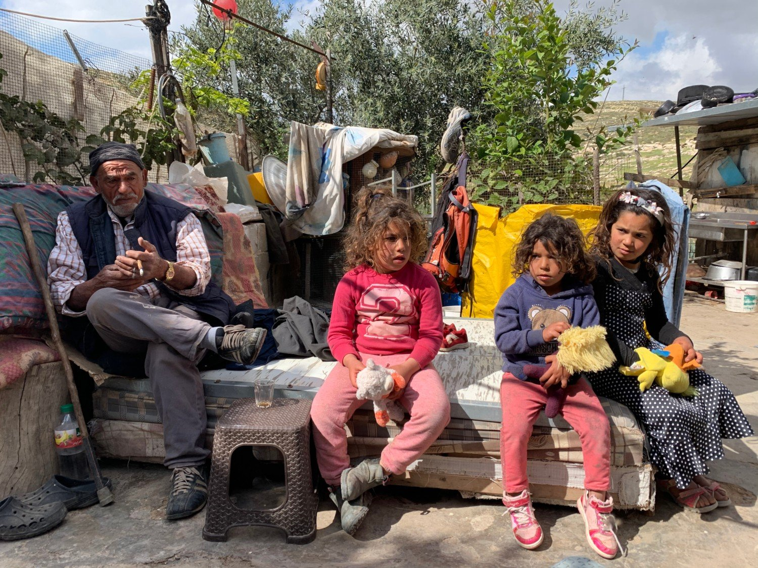 Issa Abu Kabbash with his daughters (from left) Narmin, Eman and Maram outside their home (MEE/Shatha Hammad)