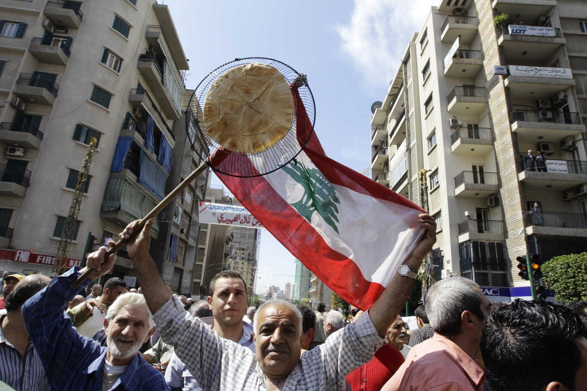 Lebanese bus and taxi drivers carry a Lebanese flag and a flatbread during an April 2010 rally in Beirut protesting fuel prices (AFP)