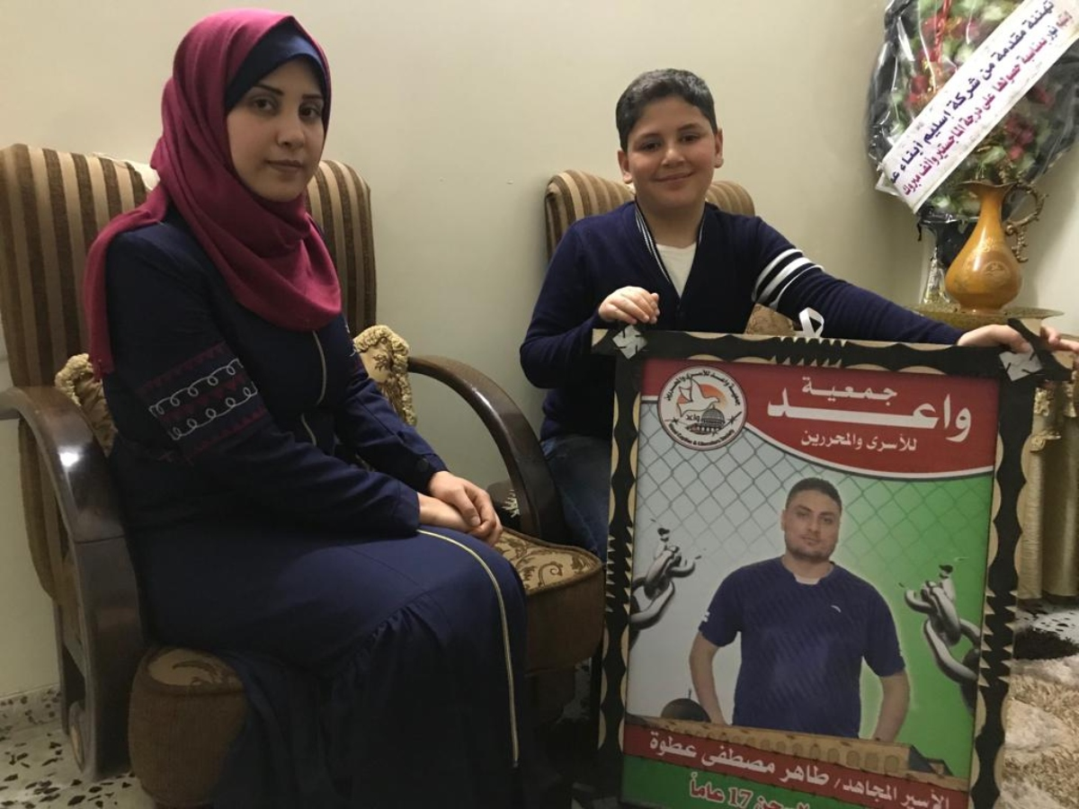 Nour and her son Mohammed pose next to a photograph of her husband Taher (MEE/Motasem Dalloul)
