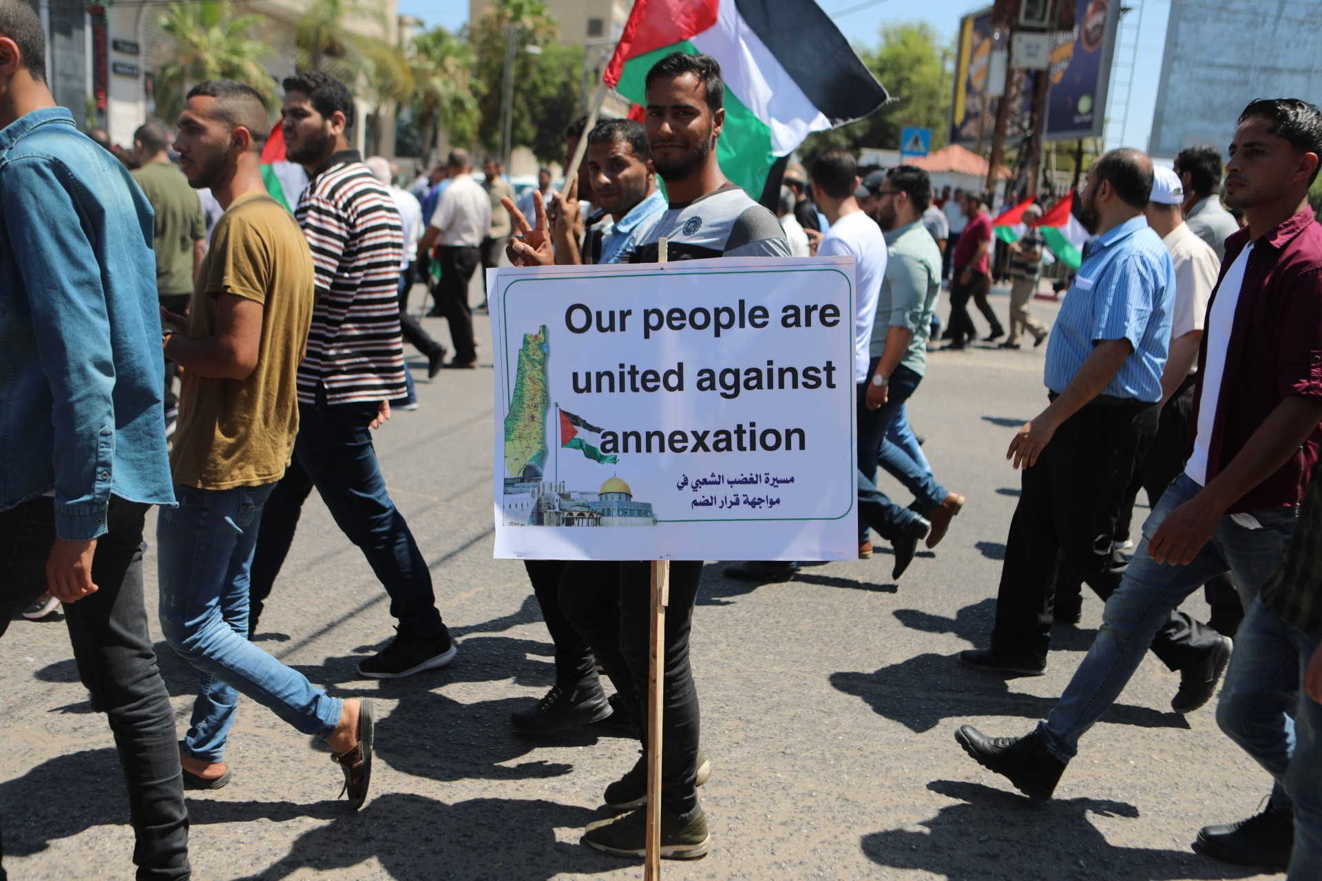 A Palestinian carrying a placard during a protest against Israeli annexation in the Gaza City on 1 July 2020 (MEE/Mohammed Hajjar)