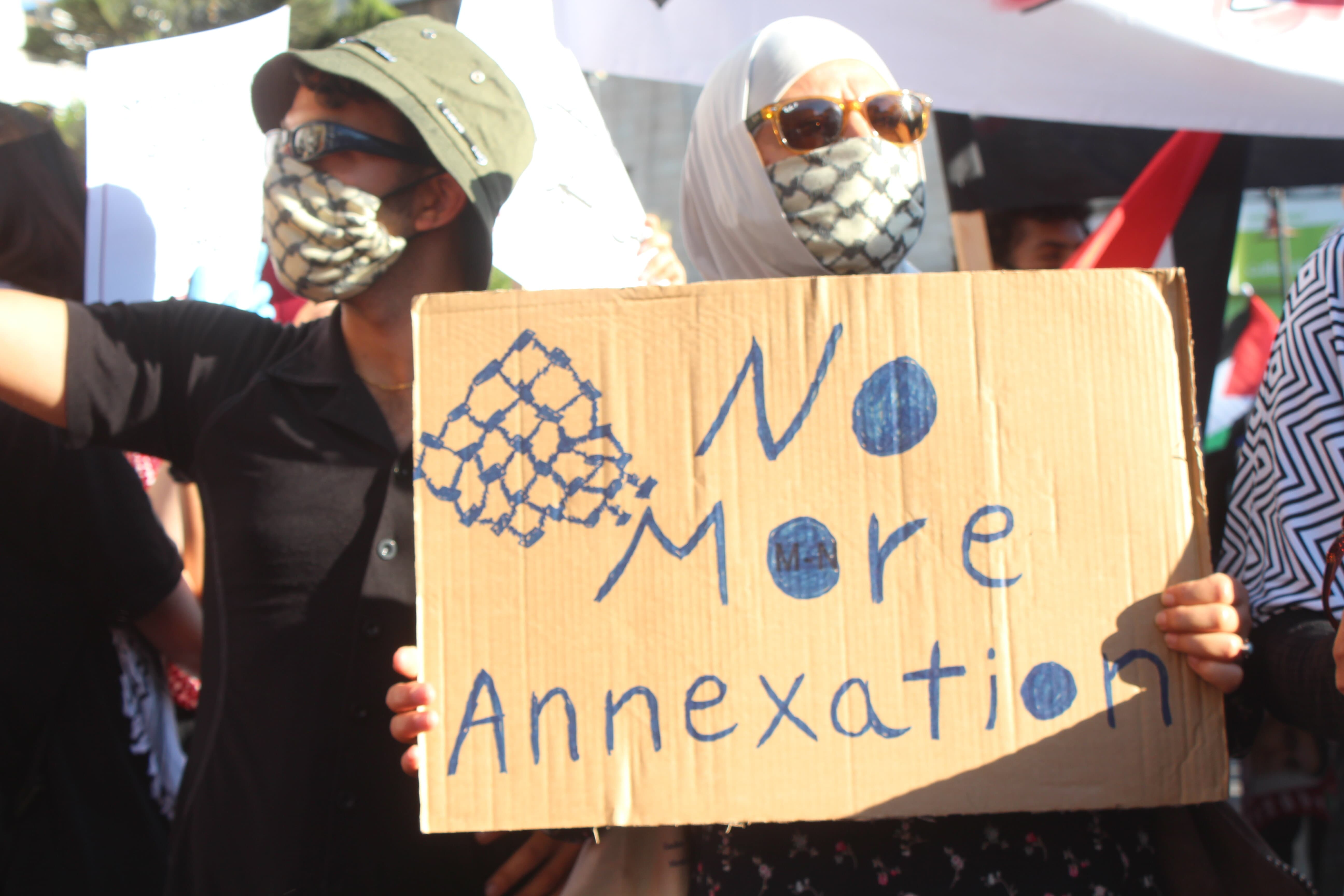 A demonstrator holds up a sign saying 'No more annexation' at a protest in Ramallah on 1 July