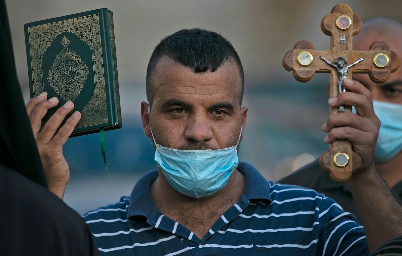 Un Palestinien tient une croix et un Coran lors d'une manifestation contre les propos du président Emmanuel Macron sur les caricatures du prophète Mohammed, à Bethléem, le 28 octobre 2020 (AFP)