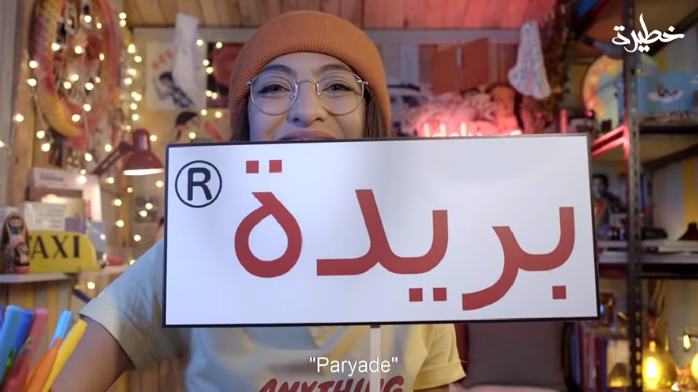 "Maria holds up a sign reading ""to period"" in Arabic (screengrab)"