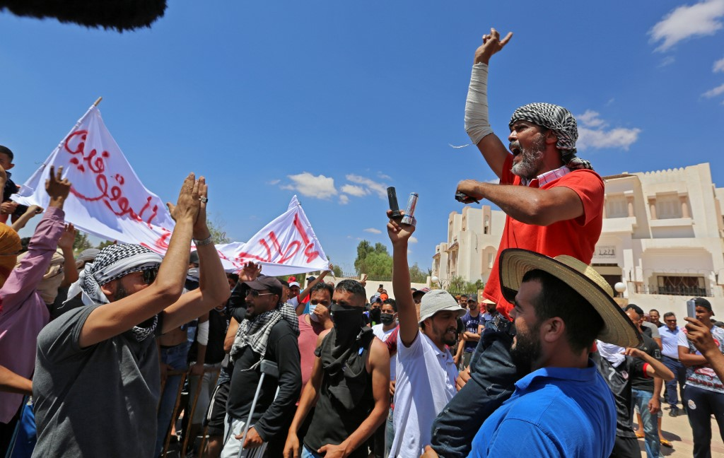 Tunisian chant slogans during a gathering, to demand the release of detained protesters who were tried for disrupting public order, in front of the local court in Tataouine on June 23, 2020.