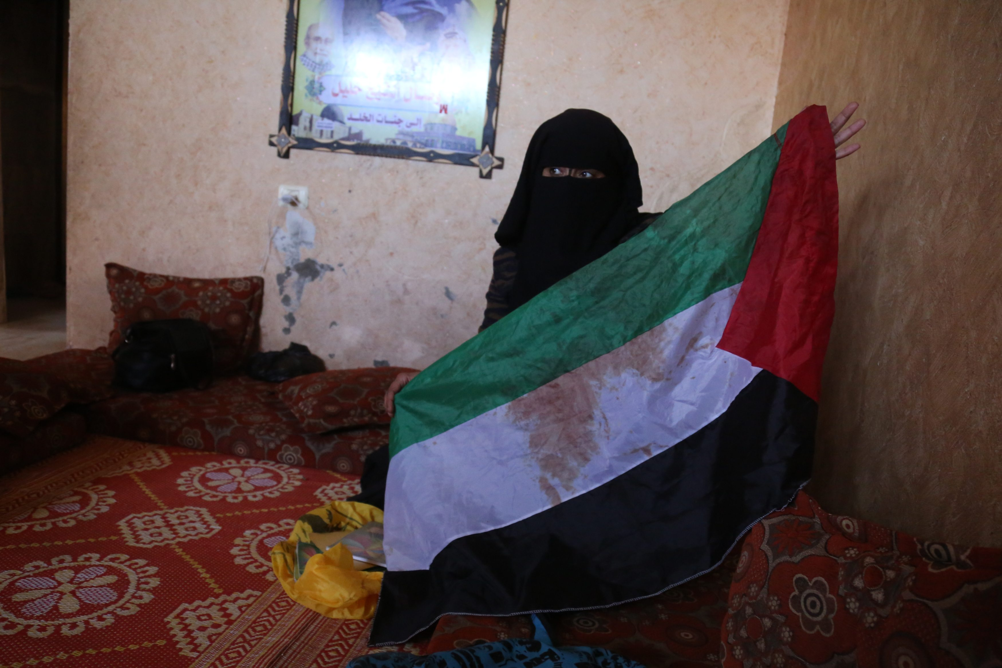 Reem Abu Irmana holds up the bloodied Palestinian flag her daughter Wassal would wave during demonstrations (MEE/Samar Abu Elouf)