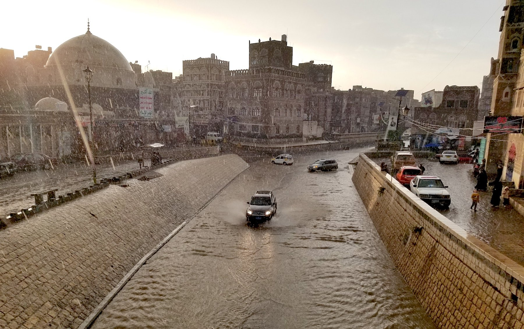 Cars driving through flooded road in Old City of Sanaa, Yemen