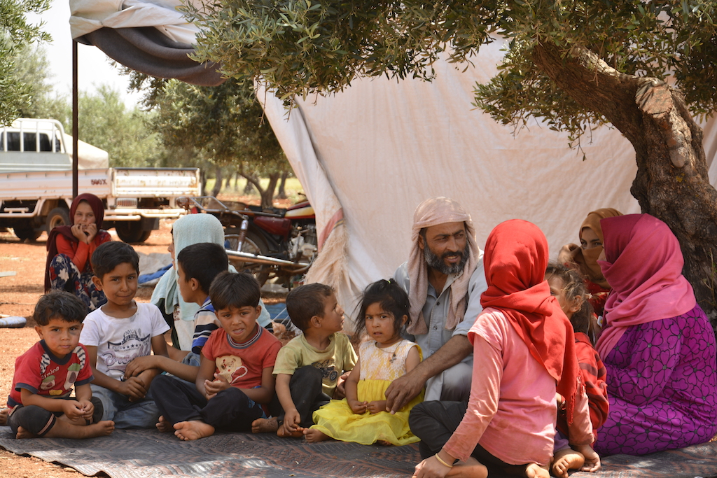 Abdul Aziz al-Kder, sitting with his wife and seven children under olive trees in random Camp on the road of Atme (Harun al-Aswad)