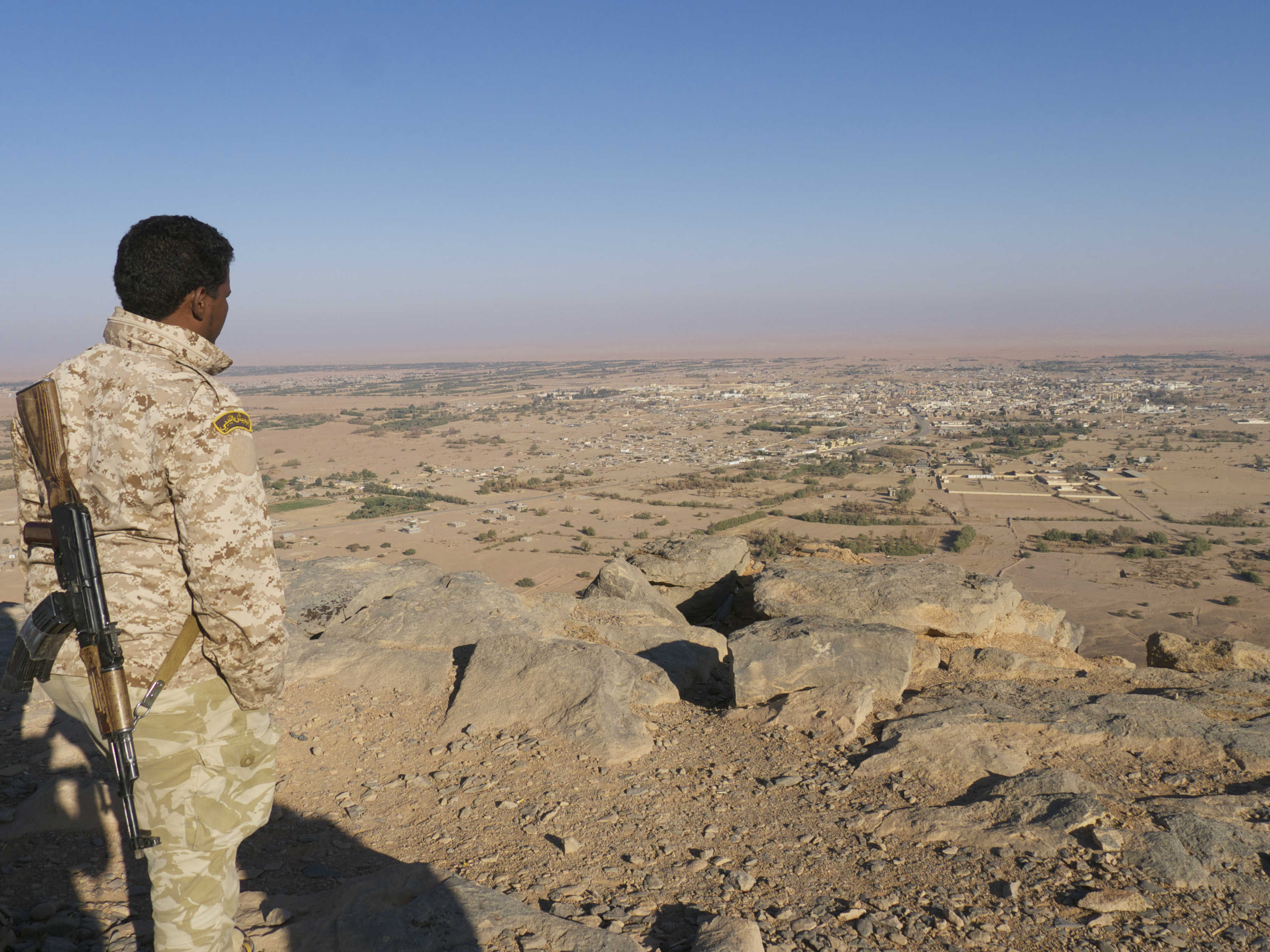 A Tuareg fighter overlooking Ubari from a mountain in 2015 (MEE/Tom Wescott)