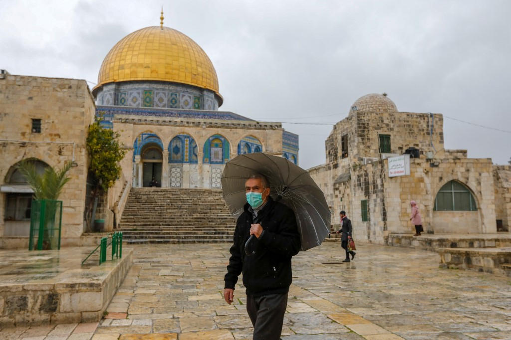 A man wears a face mask to protect against coronavirus inside the almost-deserted al-Aqsa Mosque compound in Jerusalem on 20 March (AFP)