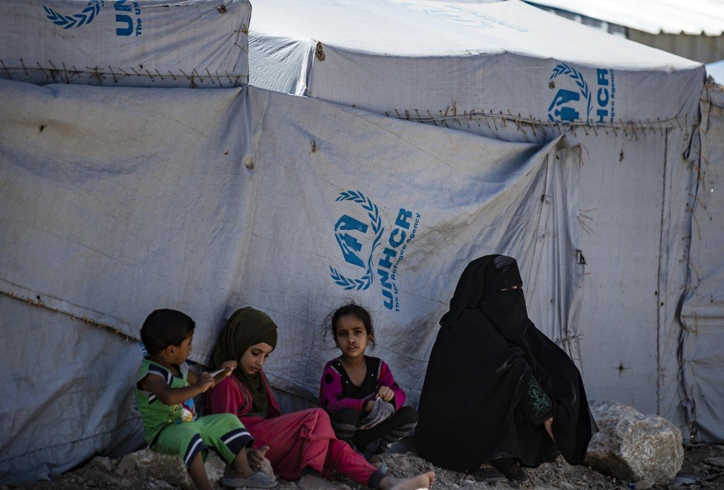 Members of a displaced family sit outside a tent in Syria's al-Hol camp on 25 August (AFP)