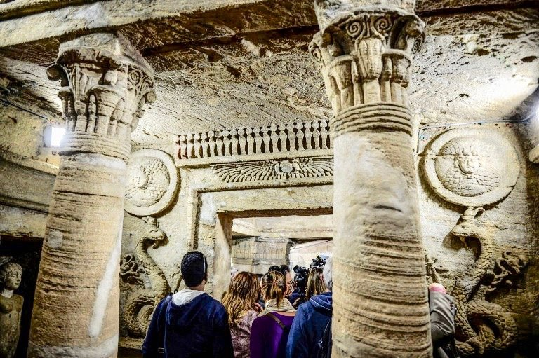 Visitors tour catacombs in Alexandria, Egypt, on Sunday (AFP)