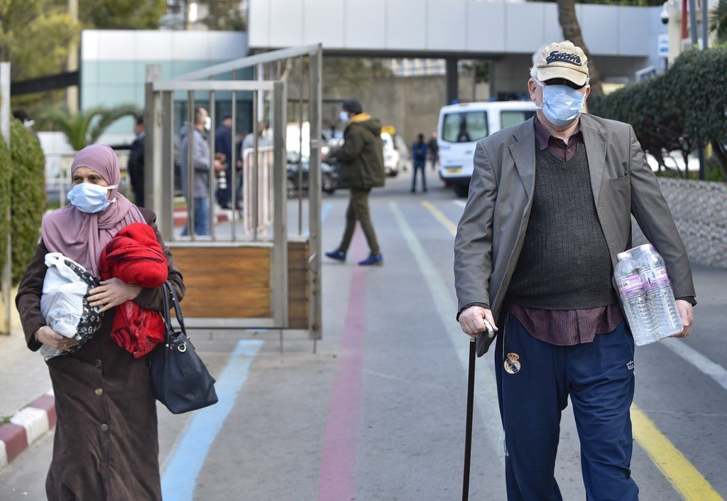 People wear protective masks in Algiers on 26 February (AFP)