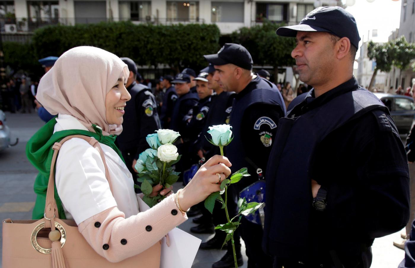An Algerian protester offers roses to police during protests by teachers, lawyers and officials in several cities across the country on Wednesday, 13 March (Reuters)