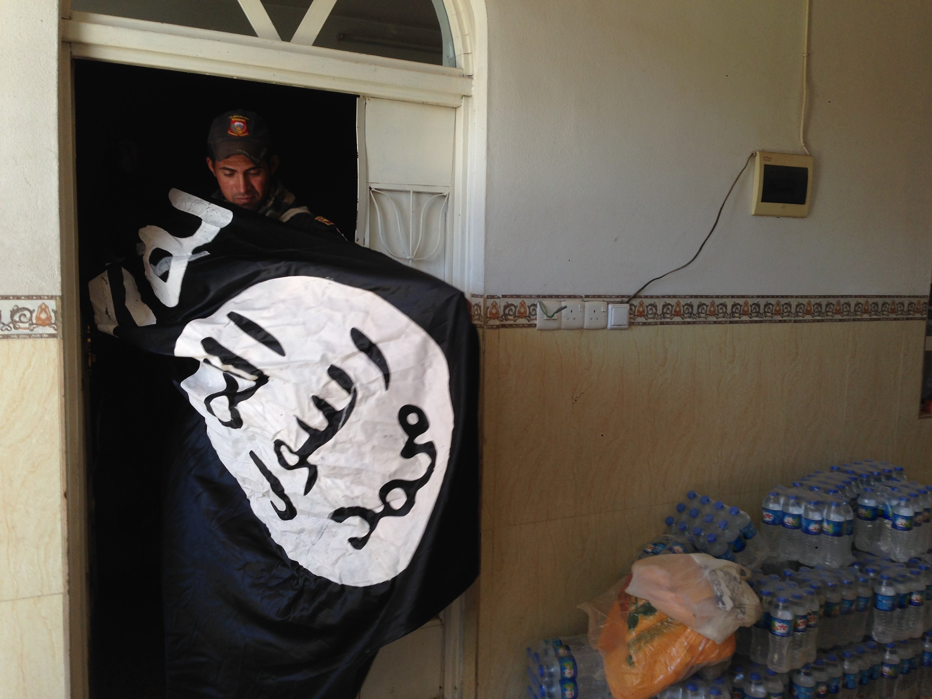 An Iraqi Special Forces soldier finds an IS flag in Mosul (MEE/Tom Westcott)