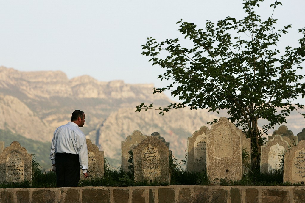 A Kurdish man examines gravestones at a monument to those killed during an Anfal attack in Sewsenan in 2006 (AFP)
