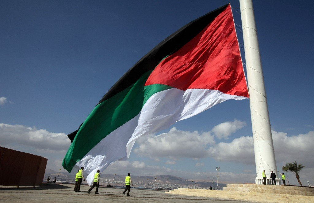 A giant Jordanian flag is raised during a celebration in the port of Aqaba in 2016 (AFP)
